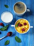 Healthy eating, food  and diet concept - Cornflakes  with berrie. S, milk and coffee for breakfast. Blue wooden background. Top view Royalty Free Stock Photo