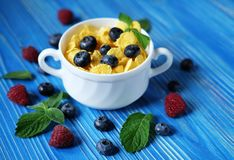 Healthy eating, food  and diet concept - Cornflakes with berries. Raspberries and blueberries  on blue wooden background. Top view. Close up Royalty Free Stock Photo