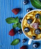Healthy eating, food  and diet concept - Cornflakes with berries. Raspberries and blueberries  on blue wooden background. Top view. Close up Stock Images