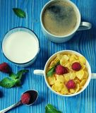 Healthy eating, food and diet concept - Cornflakes with berries raspberries and blueberries on blue wooden background. Healthy eating, food  and diet concept Stock Image