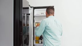 Man taking apple from fridge at home kitchen stock video footage