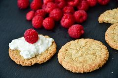 Raspberry and cookies. Healthy eating, food, dieting - oat cookies with  fresh raspberry soft cheese on black slate Royalty Free Stock Photos