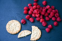Raspberry and cookies. Healthy eating, food, dieting - oat cookies with  fresh raspberry soft cheese on black slate Royalty Free Stock Image