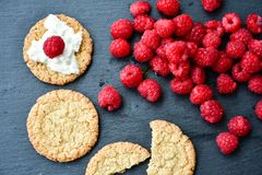 Raspberry and cookies. Healthy eating, food, dieting - oat cookies with  fresh raspberry soft cheese on black slate Royalty Free Stock Photo