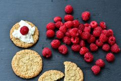 Raspberry and cookies. Healthy eating, food, dieting - oat cookies with  fresh raspberry soft cheese on black slate Stock Photos