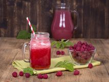 Raspberries juice smoothie shake in glass mug and raw raspberry on wooden background, close up Stock Photography