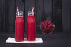 Raspberries juice in a two glass bottle and raw raspberry on black wooden background, close up. Healthy eating, food, dieting and vegetarian concept - red Stock Photography