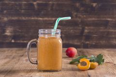 Healthy eating, food, dieting and vegetarian concept - smoothie from apricot and peach in glass mug. Fresh apricot and juice on wo. Healthy eating, food, dieting royalty free stock photos