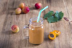 Healthy eating, food, dieting and vegetarian concept - smoothie from apricot and peach in glass mug. Fresh apricot and juice on wo. Healthy eating, food, dieting royalty free stock photography