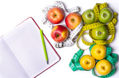 Healthy Eating: Fresh apples, measuring tape and notepad on whit Royalty Free Stock Photography