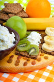Healthy eating. Fresh fruit, cornflakes and dry loaves with curd. On a wooden background Stock Image