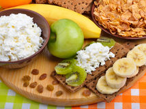 Healthy eating. Fresh fruit, cornflakes and dry loaves with curd. On a wooden background Stock Photos