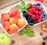 Healthy eating - fresh organic berry fruits and apricot in bowl. On rustic table stock photos