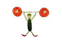 Healthy eating. Funny little man of the cucumber slices raises t Royalty Free Stock Images