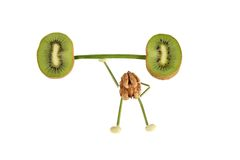 Healthy eating. Funny little people of the walnut raises kiwi ba Royalty Free Stock Images