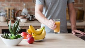 Healthy eating habit man fruit juice natural drink. Healthy eating habit. unrecognizable man holding a glass of freshly squeezed fruit juice. natural organic stock photography