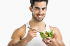 Healthy Eating. Handsome young man eating a healthy salad, isolated over a gray background Royalty Free Stock Photos