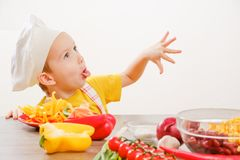 Healthy eating. Happy child prepares and eats vegetables in kitchen royalty free stock photos