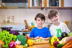 Healthy eating. Happy children prepares and eats vegetable salad Royalty Free Stock Image