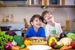 Healthy eating. Happy children prepares and eats vegetable salad Stock Photography