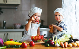Healthy eating. Happy children prepares vegetable salad in kitc royalty free stock images