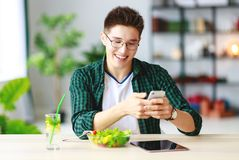 Healthy eating. happy young asian man eating salad with phone and tablet pc in morning stock photos
