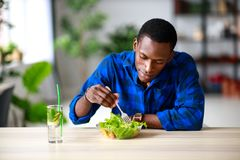 Healthy eating. happy young black man eating salad in morning in kitchen stock images