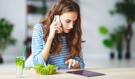 Healthy eating. happy young girl eating salad with tablet pc in morning in kitchen royalty free stock photos