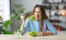 Healthy eating. happy young girl eating salad in the morning in kitchen stock image