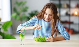 Healthy eating. happy young girl eating salad in morning in kitchen stock photo