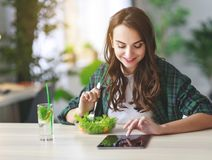 Healthy eating. happy young girl eating salad with tablet pc in the morning in kitchen stock images