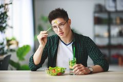 Healthy eating. happy young man eating salad in the morning in kitchen stock photography