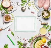Healthy eating ingredients with chicken meat around tablet with copy space on white background , top view, frame. Modern cooking. Clean diet nutrition or royalty free stock photography