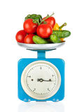 Healthy eating. Kitchen scale with vegetables isolated Stock Photo
