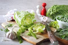Healthy eating: lettuce, garlic, green peas and tarragon. On cutting board on light background royalty free stock photos