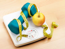 Healthy eating and living. Fresh apple and dumbbells tied with a measuring tape on a weighting scale Royalty Free Stock Images