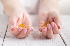 healthy eating, medicine, health care, food supplements and people concept - close up of woman hands holding pills or fish oil ca stock images