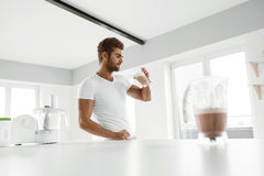 Healthy Eating. Muscular Man Drinking Sports Shake Drink Indoors. Healthy Eating. Muscular Man With Strong Muscles Drinking Protein Shake In Kitchen. Athletic stock images