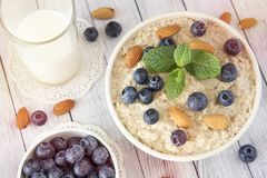Oatmeal porridge.Breakfast cereals with blueberries and glass of royalty free stock image