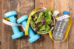 Healthy eating. Salad with water and dumbbell Stock Photography