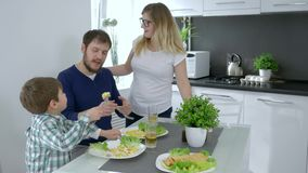 Healthy eating, small boy feeds mother during family breakfast. In home stock video