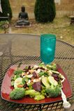 Healthy eating: Summer salad with a tumbler of sparkling water, blessed Buddha statue, outside in the yard, Broadview, Seattle, Wa