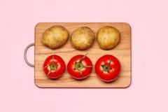Three Fresh Potatoes Near Three Tomatoes Royalty Free Stock Images