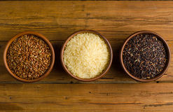 Healthy Eating, three kinds of rice: black, red and white on a w Stock Images