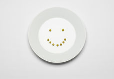 Healthy eating topic: green peas lying on a white plate on a white table in the studio, cheerful smile top view Stock Photography