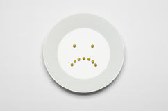 Healthy eating topic: green peas lying on a white plate on a white table in the studio, a sad smile top view Stock Image