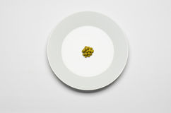 Healthy eating topic: green peas lying on a white plate on a white table in the studio top view Stock Image