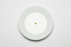 Healthy eating topic: green peas lying on a white plate on a white table in the studio top view Stock Images