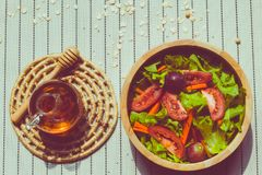 Healthy eating and traditional bakery concept. Healthy eating and traditional breakfast concept; fresh salad on the kitchen table with beverage at morning stock image