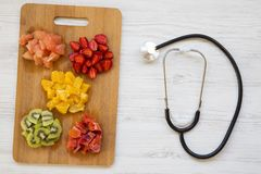 Healthy eating. Various chopped fruits with stethoscope, top view. Flat lay. From above royalty free stock images